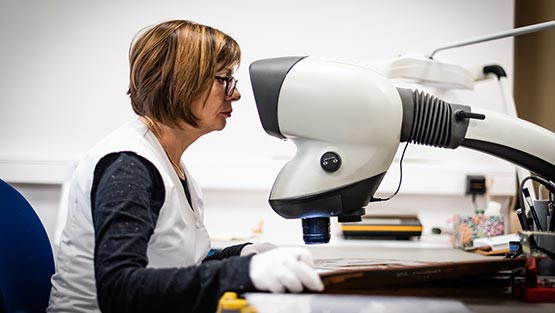 Un femme vérifiant la qualité d'un circuit imprimé flex électroniquement